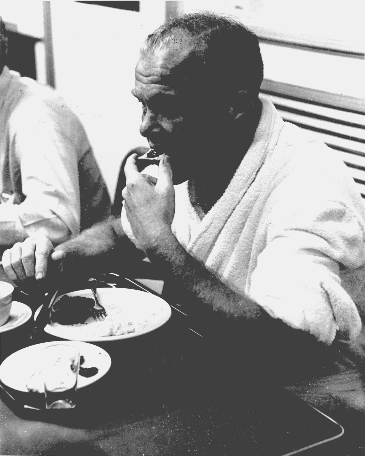 Photograph of Astronaut John H. Glenn, Jr. Eating in Crew's Quarters