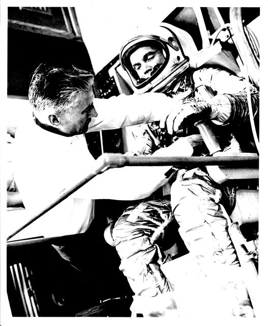 Photograph of Astronaut John H. Glenn, Jr. Having Adjustments Made to His Spacesuit