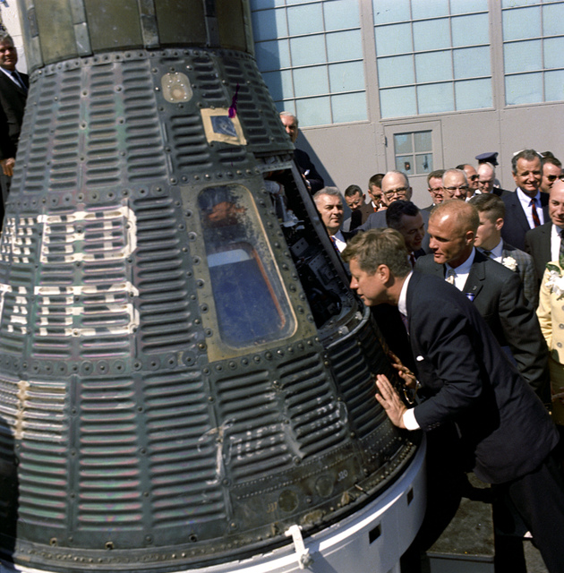 President John F. Kennedy Peers into Space Capsule at the Presentation Ceremony of NASA Distinguished Service Medal (DSM) to Astronaut and Colonel John Glenn, Jr. at Hangar 'S' at Cape Canaveral, Florida