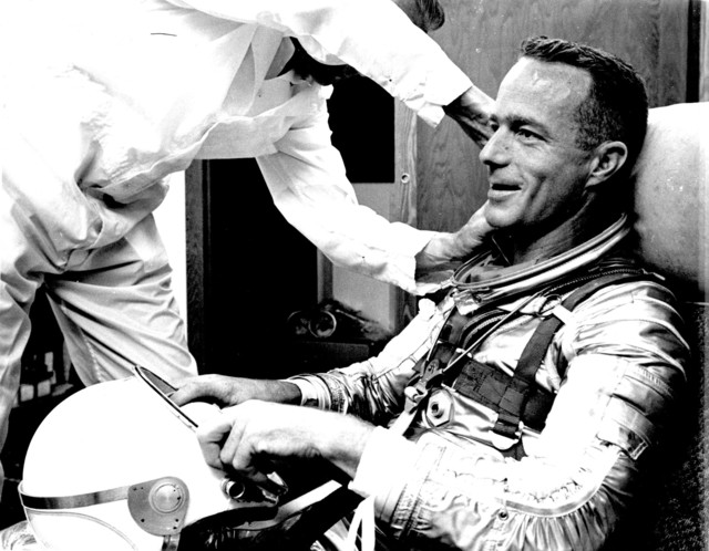 Photograph of a Suit Technician Adjusting Astronaut Malcolm Scott Carpenter's Collar Prior to Aurora 7 Launch