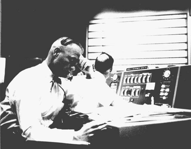 Photograph of Astronaut John H. Glenn Listening to Communications with Astronaut Malcolm Scott Carpenter during the Aurora 7 Flight
