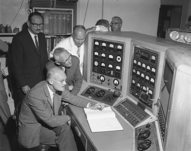"""Shutdown of 60-inch cyclotron at Crocker Lab. Clockwise from lower left: Bob Thornton Donald Cooksey, Ed McMillan (standing left), and John Lawrence at control panel. Photo taken 6/22/1962. 60""""-619. Principal Investigator/Project: Crocker Lab/60-inch"""