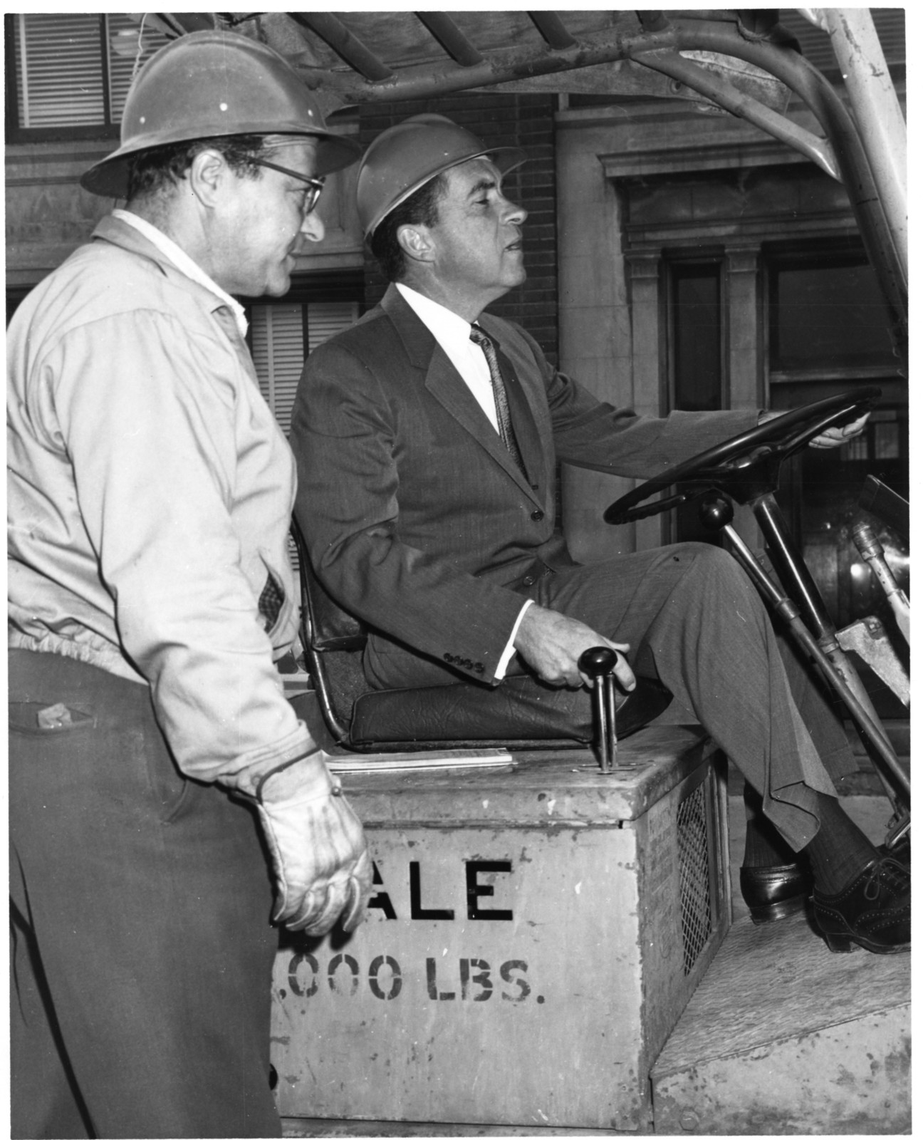 Richard Nixon wears a hard hat and drives a fork lift while visiting