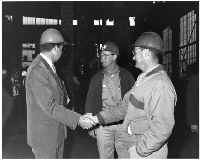 Richard Nixon wears a hard hat and shakes hands with a worker while visiting the Bethleham Steel plant in San Francisco, California