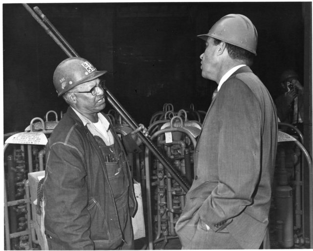 Richard Nixon wears a hard hat and speaks with a worker while visiting the Bethleham Steel plant in San Francisco, California