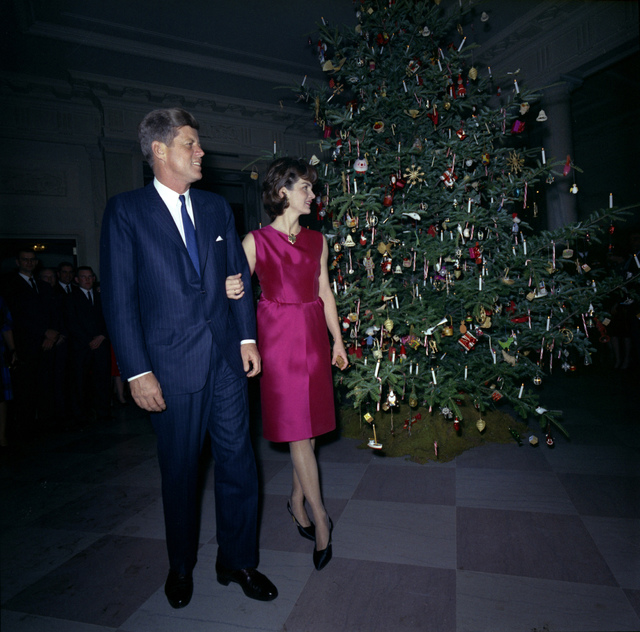 President and Mrs. Kennedy Make an Appearance at the White House Staff Christmas Party near the Christmas Tree in the Cross Hall