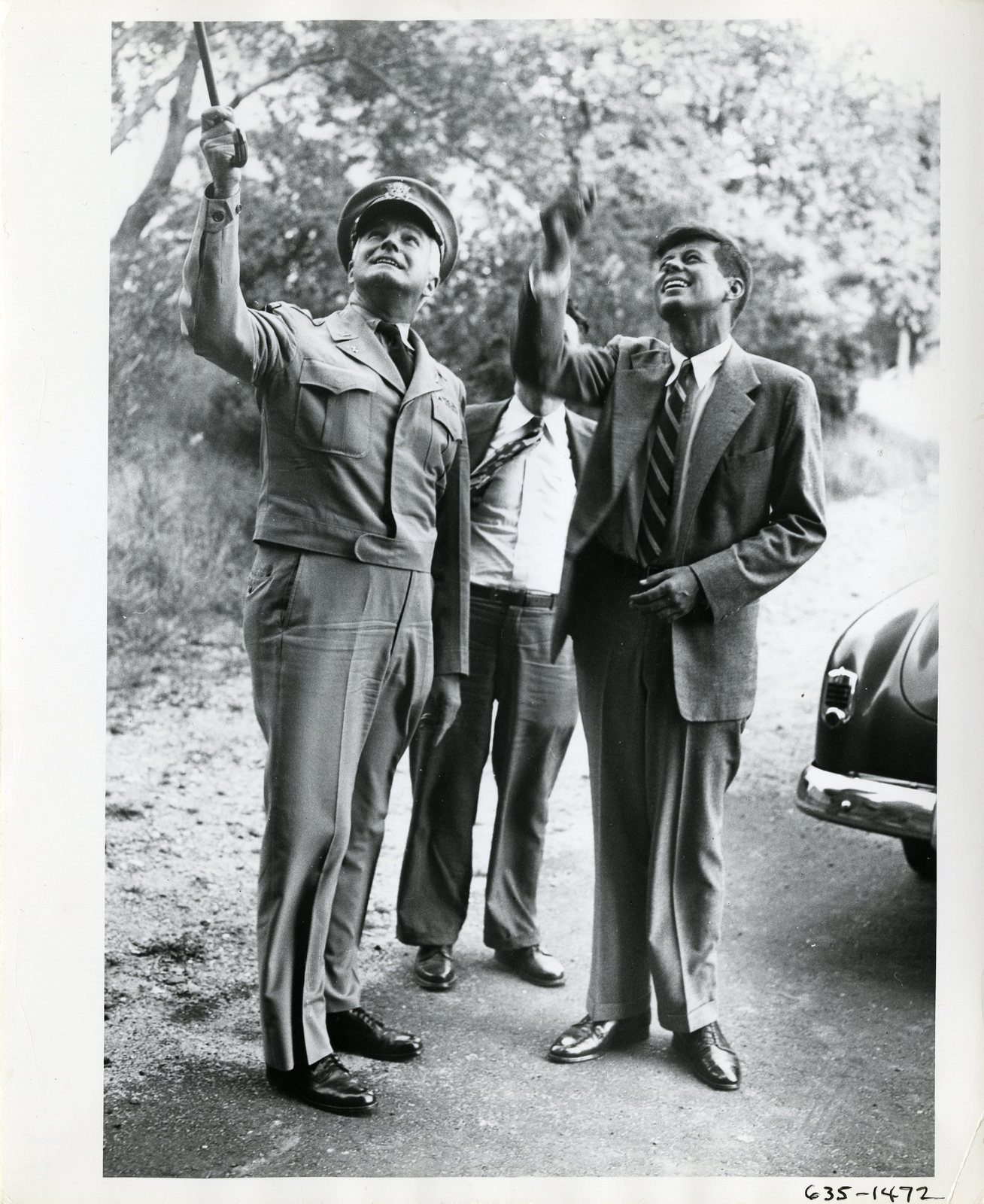Senator John F. Kennedy and an Officer Stand Outside on a Road, Both Pointing Up