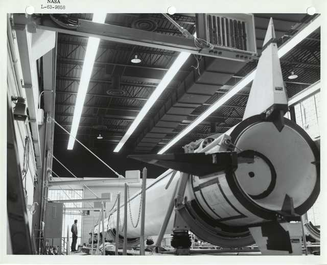 Photograph of a Scientist Standing next to a Rocket inside of a Warehouse