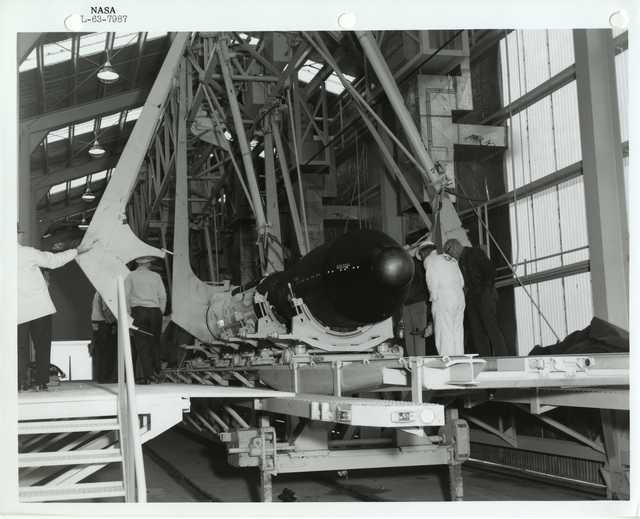 Photograph of Scientists Examining and Preparing a Rocket inside of a Holding Structure