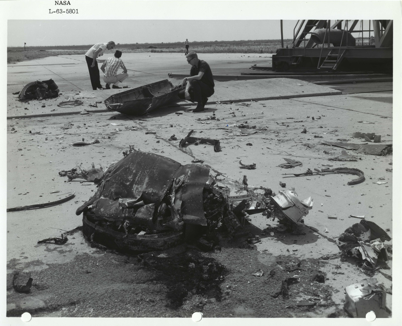 Photograph of Three Scientists Examining Debris after a Launch at the Wallops Island Launch Area in Virginia