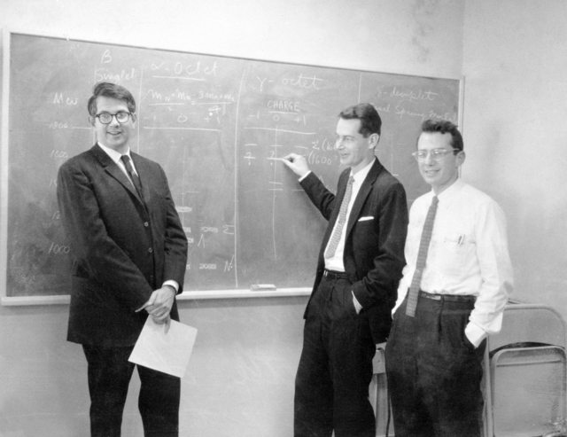 """New evidence for the """"eight-fold way"""" theory of strong interactions are, left to right: Sheldon Glashow, George Kalbfleisch, and Arthur Rosenfeld. Blackboard notation show how the newly discovered particle, the Y*-1, fits into an unfilled octet of the """"eight-fold way"""" taken January 4, 1963. See also XBD201004-00278. Morgue 1963-127 (P-1). [Photographer: Donald Cooksey]"""
