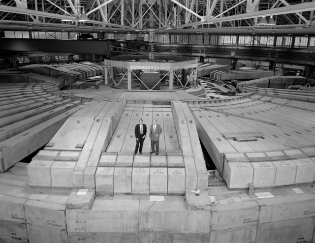 """Wide-angle view of the remodeled Bevatron shows extensive new shielding, including seven-foot-thick concrete roof and """"igloo"""" at hub with Lawrence Radiation Laboratory Director Edwin McMillan, left and Bevatron Group Leader Edwin Lofgren. Photo taken January 30, 1963. Morgue 1963-3 (P-1) [Photographer: Donald Cooksey]"""