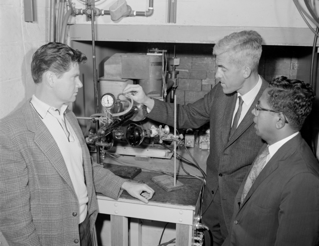 Irradiation tube at 4.5 MeV linear accelerator. Shown with apparatus are three members of the research team which recently succeeded in synthesizing adenine (left to right) Doug Pounds, Richard Lemmon and Cyril Ponnamperuma. Photo taken May 23, 1963. Morgue 1963-16 (P-1) [Photographer: Donald Cooksey]