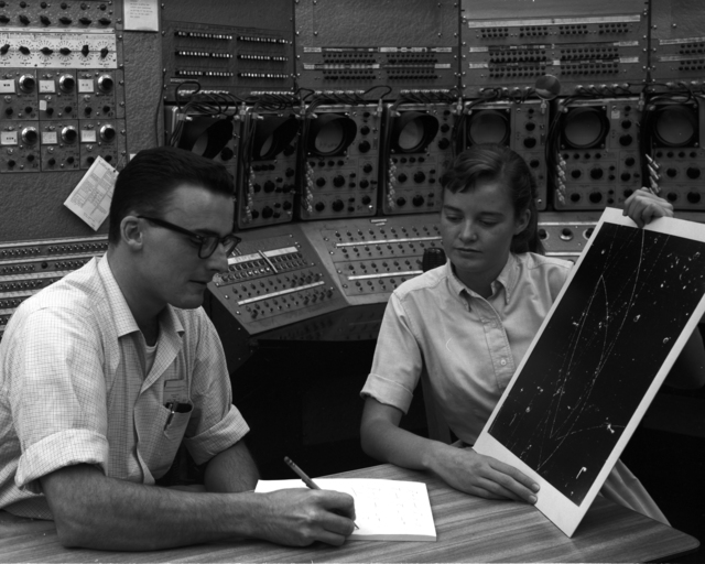 Bob West and Bonnie Thompson of the Alvarez Group looking at a track picture in the Bevatron control room, taken October 2, 1963. Morgue 1959-25 (P-3). Photo taken for J. Walter Thompson.
