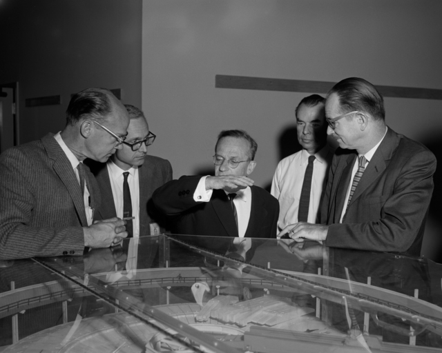 Ed Lofgren (left), Edwin McMillan (right), and Vladimir Veksler, Russian experimantal physicist (center) with the Bevatron model, taken October 28, 1963. Morgue 1963-35 (P-1) [Photographer: Donald Cooksey]