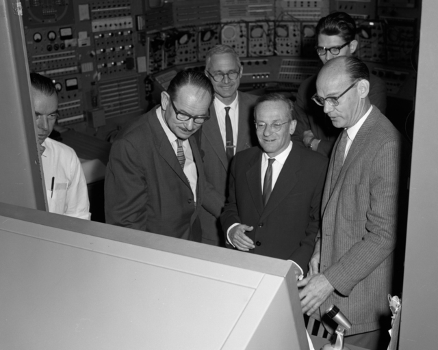 From right to left, front: Edward Lofgren, Vladimir Veksler, Russian experimantal physicist, and Edwin McMillan in the Bevatron control room, taken October 28, 1963. Morgue 1963-35 (P-8) [Photographer: Donald Cooksey]