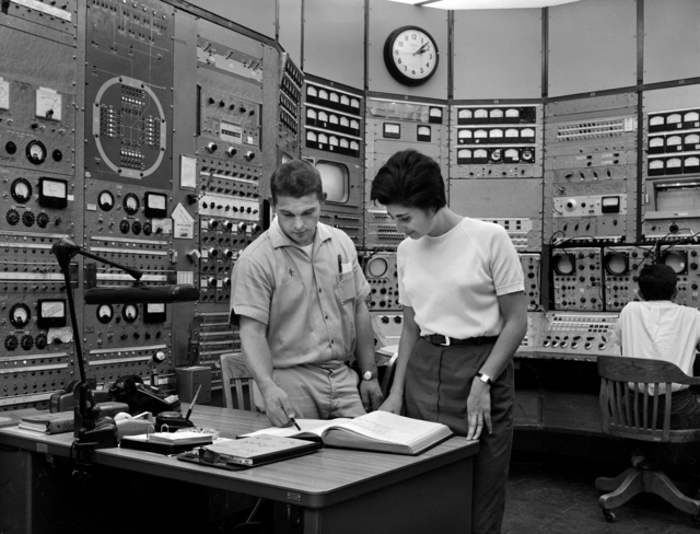 Physicist Angelina Galtieri, right consults log with operator in control room of the Bevatron. Photo taken November 13, 1963. Morgue 1963-39 (P-1) [Photographer: Donald Cooksey]
