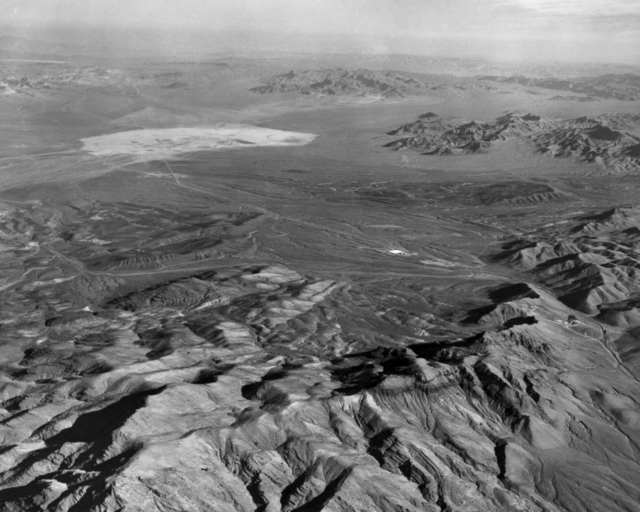 Aerial view of the Nevada Test Site taken from a point near Mercury. The view is toward the northeast, over Frenchman Flat (foreground) and Yucca Flat (distant background). The mountains in the foreground and background rise to heights of about 5,000-7,000 feet. Photo taken December 1963. Morgue 1963-125 (P-1) [Photographer: Donald Cooksey]