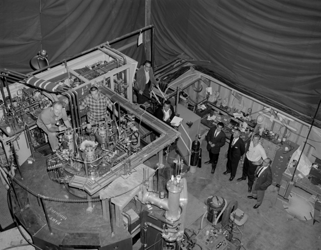 New 25-inch Bubble Chamber is shown with part of its design and development crew. Left to right: Bob Reynolds, Ron Rinta, Rod Byrns, Frank Barrera, Dan Curtis, Jim Shand, Glenn Eckman, and Paul Hernandez. Photo taken December 1963. Morgue 1963-124 (P-1) [Photographer: Donald Cooksey]