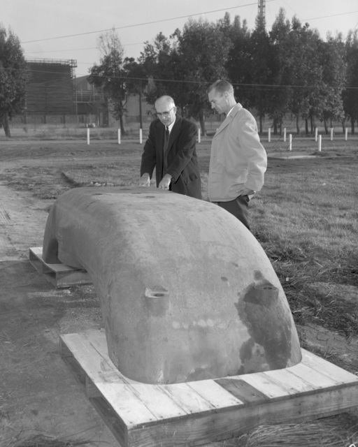Harvey White, head of the Lawrence Hall of Science project, and his assistant Jim Murphy, looking at the old 37-inch cyclotron magnet, returned from UCLA. Photo taken December 16, 1963. Morgue 1963-55 (P-7) [Photographer: Donald Cooksey]