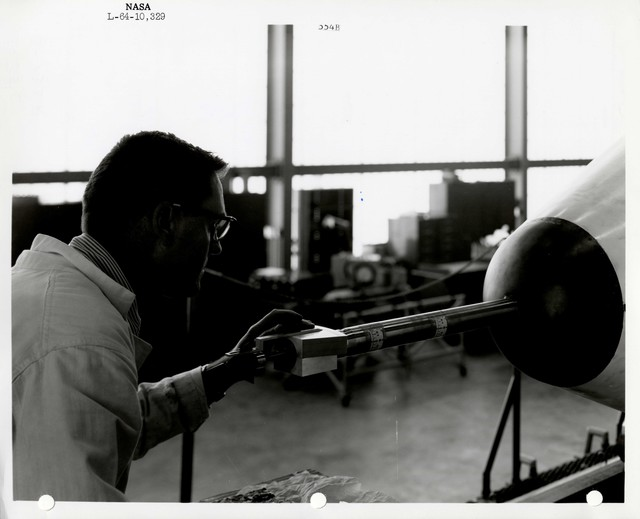 Photograph of a Scientist Examining a Rocket Part inside of a Warehouse