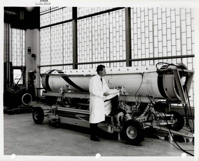 Photograph of a Scientist Examining and Taking Notes on a Rocket Part inside of a Warehouse