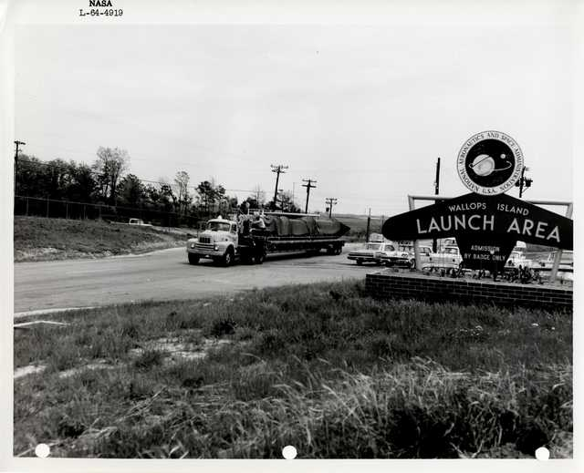 Photograph of a Vehicle Transporting a Rocket next to the Entrance Signto the Wallops Island Launch Area