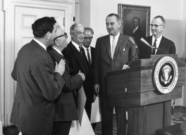 Luis Alvarez (right) receives the 1963 National Medal of Science from President Johnson, taken January 13, 1964. Morgue 1964-13 (P-3). Copy negative from Luis Alvarez print [photographer unknown]