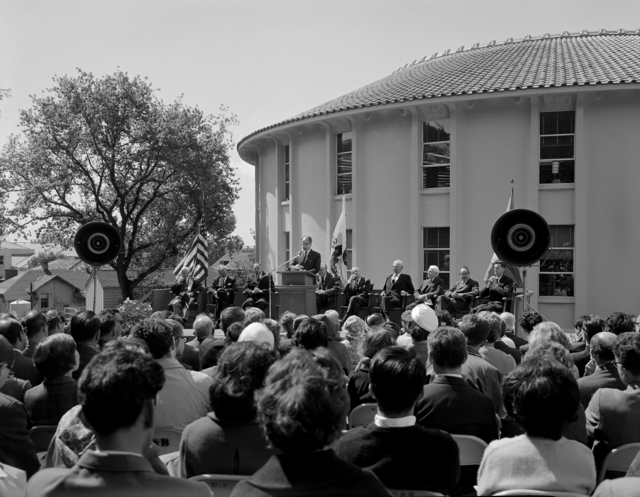 Outdoor ceremony dedicating the new Laboratory of Chemical Biodynamics (seen in background).Dr. Arne Tiselius (guest of honor) speaking. Seated on dias from left are guests Prof. Michael Goodman; Swedish Consul General Per Anger; AEC Chairman Glenn Seaborg; UC Berkeley Chancellor Edward Strong; Biodynamics Lab Director Melvin Calvin; NSF Director Leland Haworth; UC Regent Donald McLaughlin; LRL Director Edwin McMillan; UC Dean of Chemistry Robert Connick. Photo taken April 1, 1964. Morgue 1964-16 (P-1) [Photographer: Donald Cooksey]
