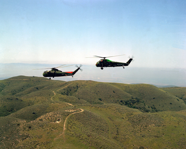 An air-to-air left side view of a CH-37C helicopter (front) from HMA-462 and a UH-34D helicopter from HMM-363 in formation during a training flight. Both aircraft are from Marine Corps Air Station Tustin, Calif