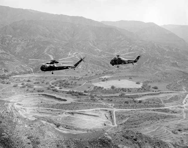 An air-to-air left side view of a CH-37C helicopter, left, from Marine Heavy Helicopter Squadron 462 (HMH-462) and a UH-34D Seahorse helicopter from Marine Medium Helicopter Squadron 363 (HMM-363). The helicopters are based at Marine Corps Air Station, Tustin, California