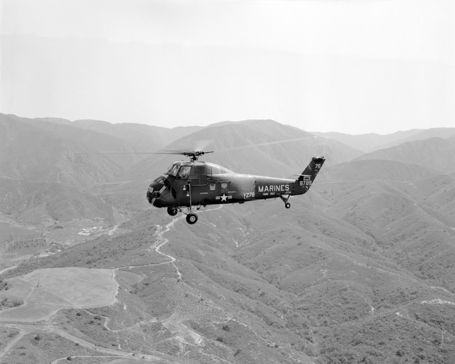 An air-to-air left side view of a UH-34D helicopter from HMM-363 returning from a training flight. The aircraft is from Marine Corps Air Station Tustin, California