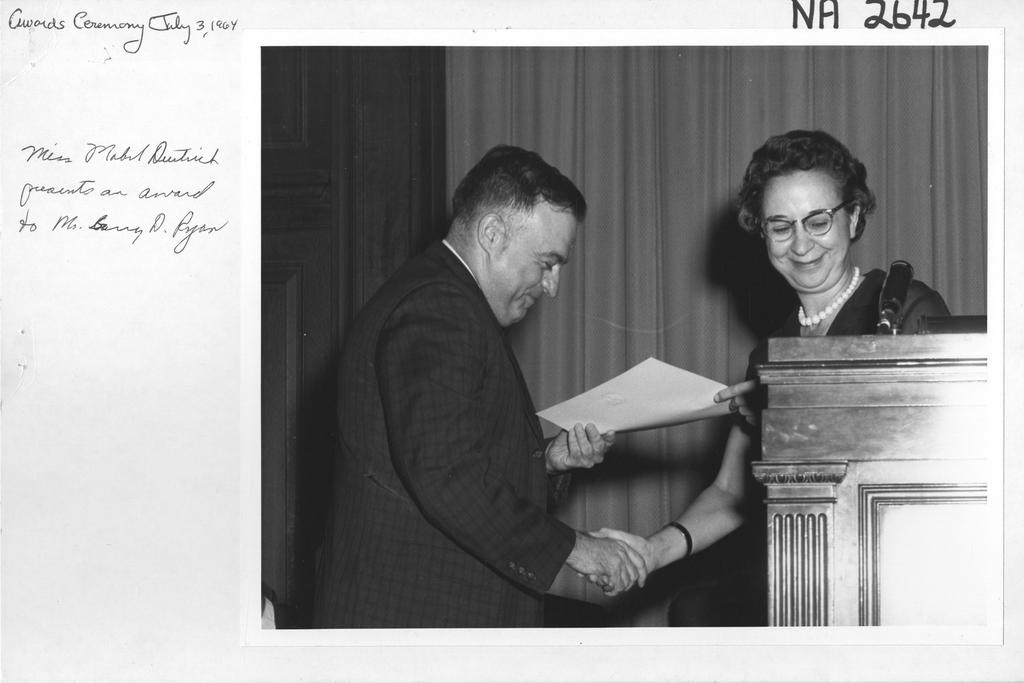 Miss Mabel E. Deutrich Presents an Award to Mr. Garry D. Ryan