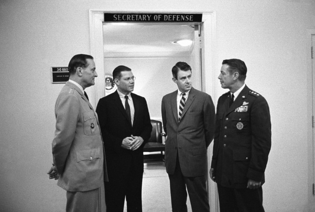 A spontaneous conference is held in a corridor at the Pentagon by, left to right, General Earle G. Wheeler, USA, Chairman, Joint Chiefs of STAFF; Secretary of Defense Robert S. McNamara, Deputy Secretary of Defense Cyrus R. Vance and Lieutenant General David A. Burchinal, USAF, Director of the Joint STAFF, Joint Chiefs of STAFF
