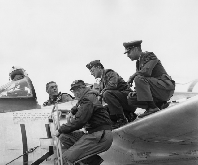 """U.S. Air Force LT. COL. Alexander P. Macdonald (Eventual North Dakota Adjutant General), assigned to the 119th Fighter Wing, North Dakota Air National Guard, sits the cockpit of an F-89 Scorpion aircraft at Hector International Field, North Dakota. To LT. COL. Macdonald's left on the wing are eventual unit Commander, LT. COL. Marsh Johnson and LT. COL. Duane""""Pappy""""Larson.  The identity of the person on the ladder is unknown. (A3604) (U.S. Air Force PHOTO) (Released)"""