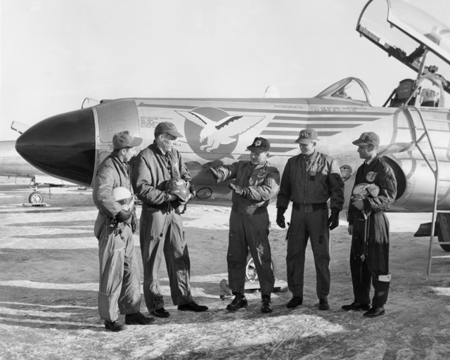 """U.S. Air Force personnel assigned to the 119th Fighter Wing""""Happy Hooligans"""", North Dakota Air National Guard, standing in front of a F-94 A/C Starfire aircraft at Hector Field, North Dakota. The""""Happy Hooligan""""pilots flew the F-94 A/C Starfire aircraft from 1954-to-1960. Pictured left-to-right are: Duane""""Pappy""""Larson; Thor Hertsgaard; Marshall Johnson; and Alexander P. Macdonald.  The person on the far left is unknown.  The ranks of the people at the time are unknown (A3604) (U.S. Air Force PHOTO) (Released)"""