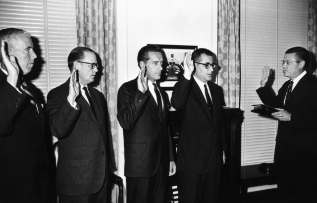 Secretary of Defense Robert McNamara administering the oath of office to (left to right) Norman Paul, Thomas Morris, John Foster, and Harold Brown, taken October 28,1965. Morgue 1965-37 (P-1) [Photographer: Donald Cooksey]