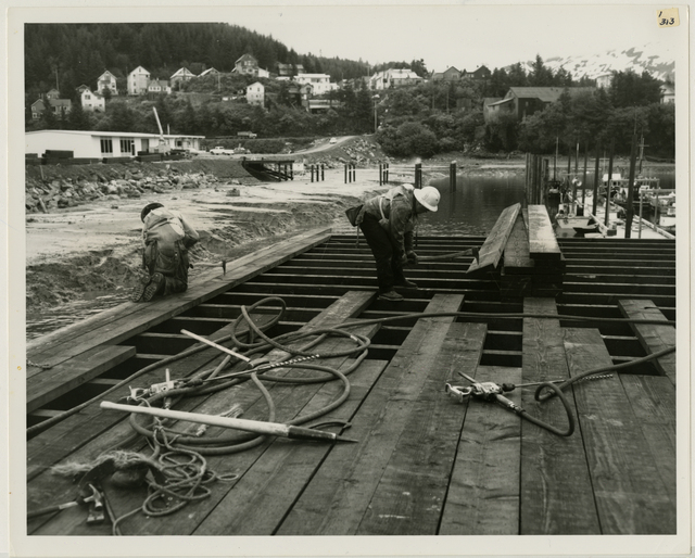 6/65. Cordova - Workman placing new planking for small boat harbor approach