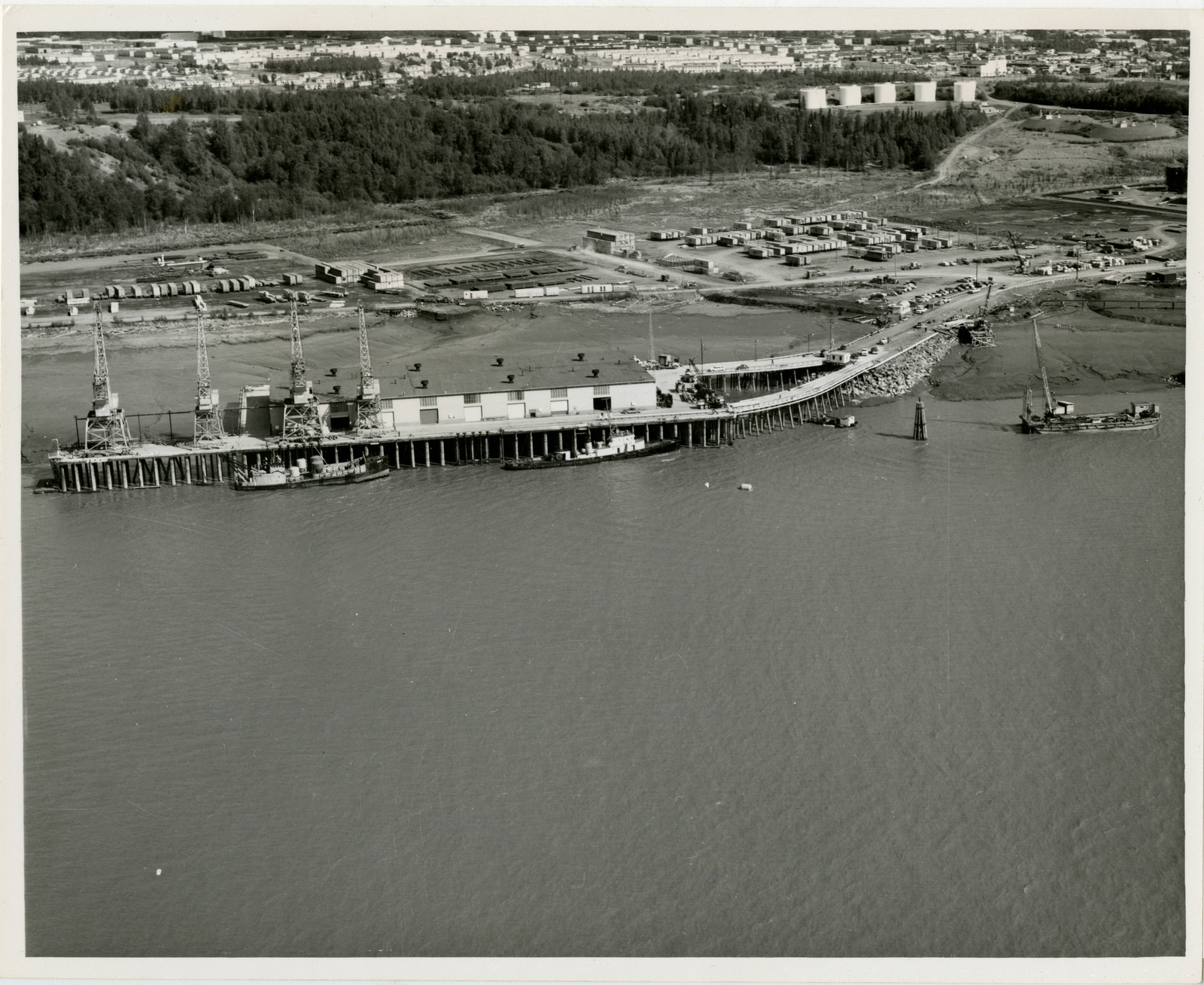 Contract 64-51 temporary port POL facilities, contractor- Gillbrough Structures, 11 June 1964, photo by Tice, complete timber dolphin on the left, barge mounted pile driver constructing breasting platform, mobile pile driver constructing trestle for pipeline looking east. Background, contract 64-27 dry cargoes storage areas, contractor- Miller Brothers. 11 June 1964, photo by Tice, dry storage areas raised and extended