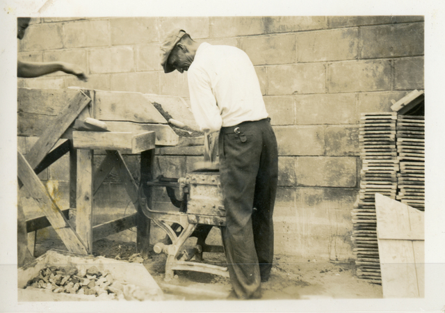 Man Tamping Concrete Blocks into a Mold