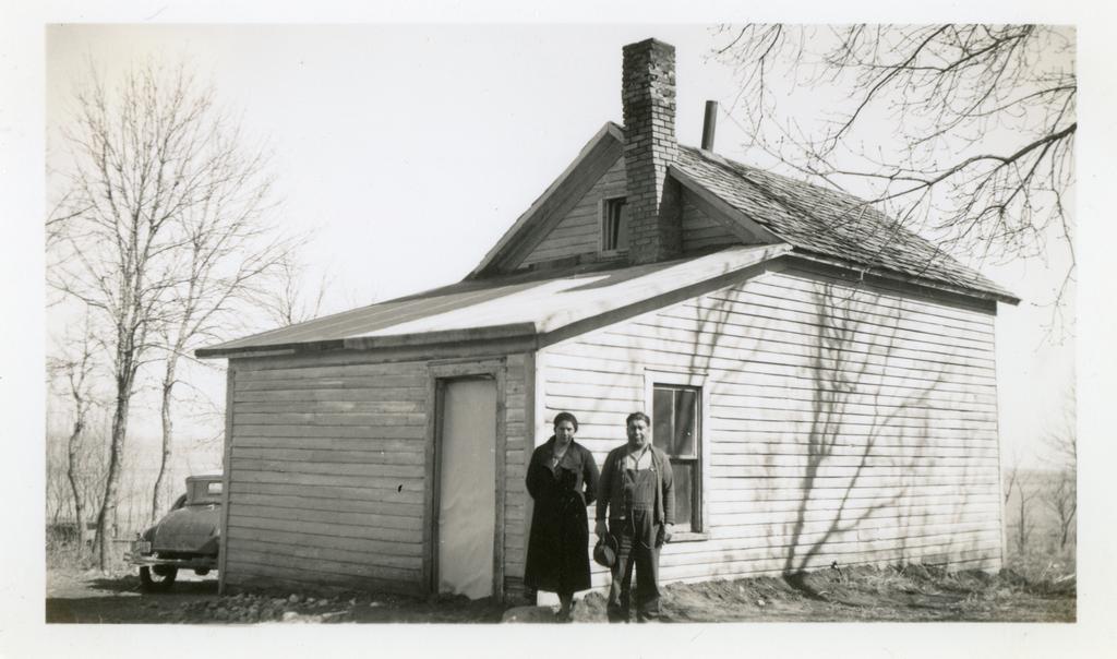 Mr. and Mrs. Ed Heminger by Home before Repairs