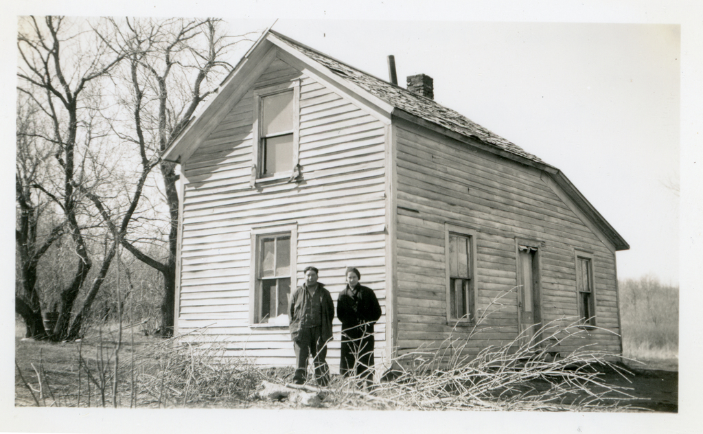 Mr. and Mrs. Ed Heminger by Home before Repairs