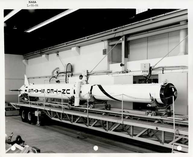 Photograph of a Scientist Examining and Working on a Rocket inside of a Warehouse