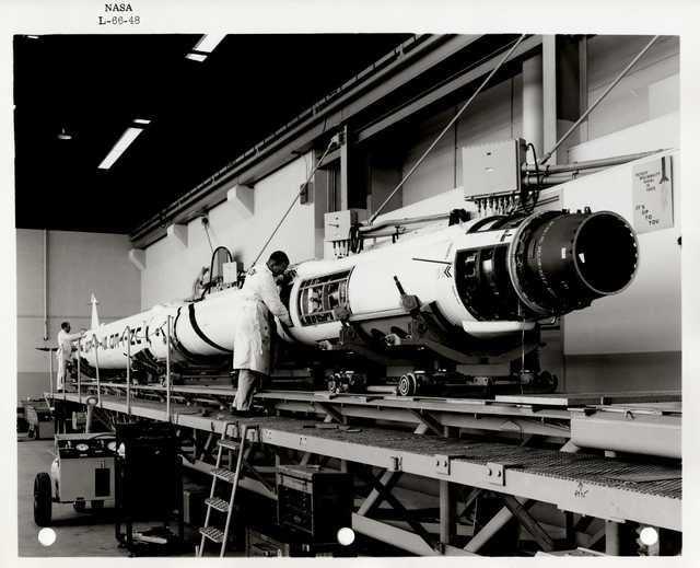 Photograph of Two Scientists Examining and Working on a Rocket inside of a Warehouse
