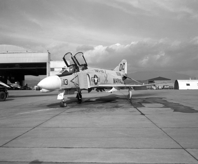A left front view of an F-4B Phantom II aircraft on the flight line. The aircraft is assigned to Marine Fighter Attack Squadron 122 (VMFA-122)