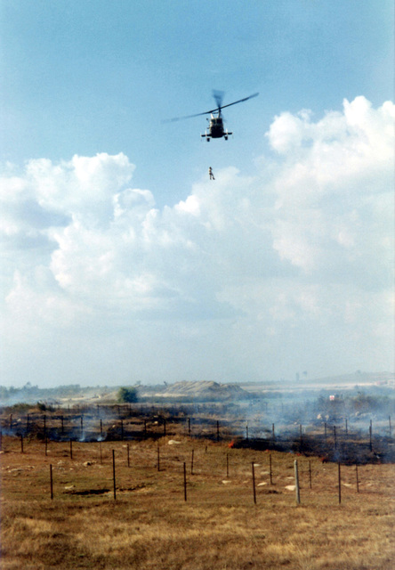 "A Kaman HH-43F Huskie (Pedro) lowers AIRMAN First Class (A1C) William Hart Pitsenbarger, USAF, Pararescue Crew Member, Detachment 6, 38th Aerospace Rescue and Recovery Squadron (ARRS) into a burning minefield at Bien-Hoa Air Base in the Republic of Vietnam (RVN) for a helicopter extraction of a wounded Vietnamese Soldier. The soldier lost a foot when he stepped on a landmine. Nobody could figure out how to extract the wounded soldier without tripping the mines. A1C Pitsenbarger said, ""No problem, just lower me down on the penetrator, Ill straddle the guy, pick him up, and then you can lift me up."" Risky as everyone knew that the prop wash could also setoff the mines. A1C Pitsenbarger..."