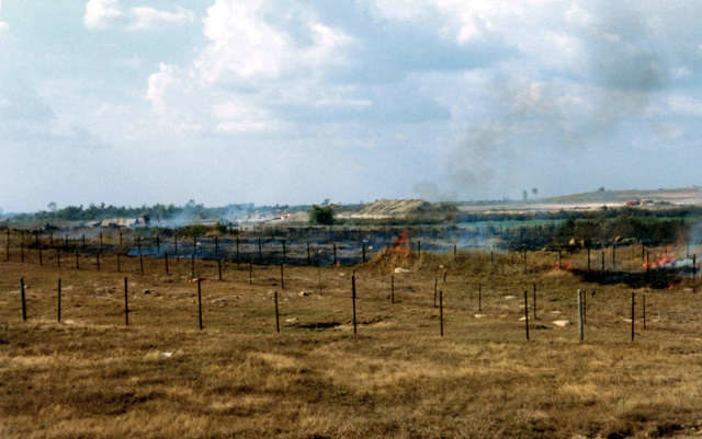 A minefield at Bien-Hoa Air Base in the Republic of Vietnam (RVN) on fire, somewhere in there an Army of the Republic of Vietnam (ARVN) soldier lies wounded after stepping on a land mine