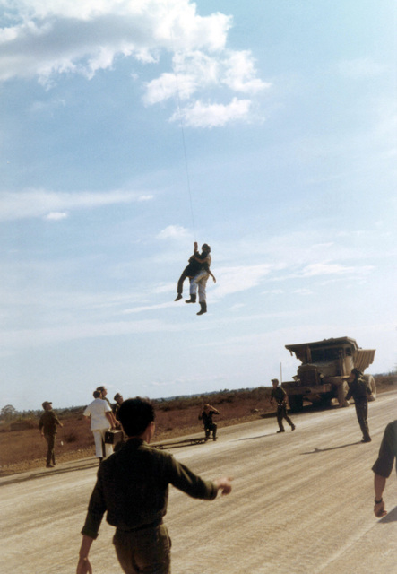 AIRMAN First Class (A1C) William Hart Pitsenbarger, Pararescue Crew Member, Detachment 6, 38th Aerospace Rescue and Recovery Squadron (ARRS) lowered onto a roadway after an extraction of an Army of the Republic of Vietnam (ARVN) soldier from a burning minefield at Bien-Hoa Air Base for immediate medical attention