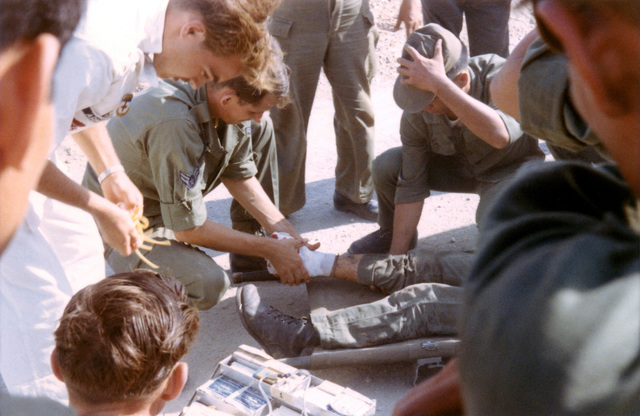 Medics treat the blown of foot of an Army of the Republic of Vietnam (ARVN) soldier immediately after he was extracted from a burning minefield at Bien-Hoa Air Base in the Republic of Vietnam (RVM)