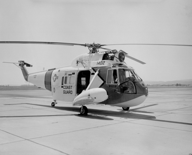 A right front view of a US Coast Guard HH-52A Sea Guard helicopter parked on the flight line